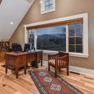 Inspiration för stora lantliga arbetsrum, med bruna väggar, ljust trägolv, ett fristående skrivbord och en dubbelsidig öppen spis