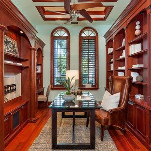 Mittelgroßes Mediterranes Arbeitszimmer ohne Kamin mit Arbeitsplatz, grüner Wandfarbe, braunem Holzboden, freistehendem Schreibtisch und rotem Boden in Miami
