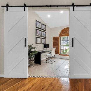 オーランドの小さいトランジショナルスタイルのおしゃれなホームオフィス・書斎 (ライブラリー、ベージュの壁、セラミックタイルの床、自立型机、ベージュの床) の写真