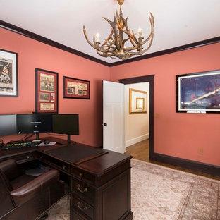 Idee per un ufficio classico di medie dimensioni con pareti arancioni, pavimento in legno massello medio e scrivania autoportante