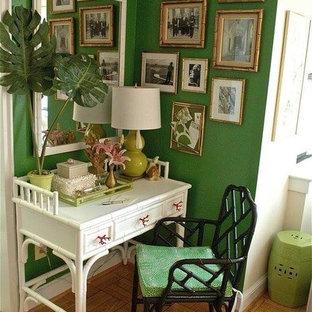 Exotisk inredning av ett litet hemmabibliotek, med gröna väggar, ljust trägolv och ett fristående skrivbord