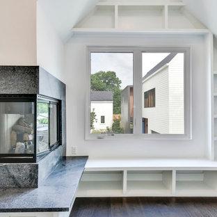 オースティンの小さいモダンスタイルのおしゃれなホームオフィス・書斎 (ライブラリー、白い壁、濃色無垢フローリング、コーナー設置型暖炉、石材の暖炉まわり、茶色い床) の写真