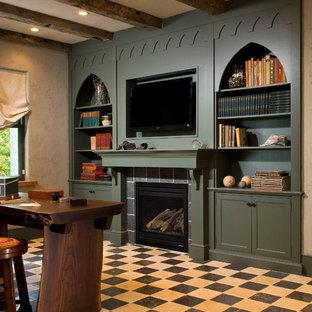 Immagine di uno studio mediterraneo con camino classico, cornice del camino piastrellata, scrivania autoportante e pavimento multicolore