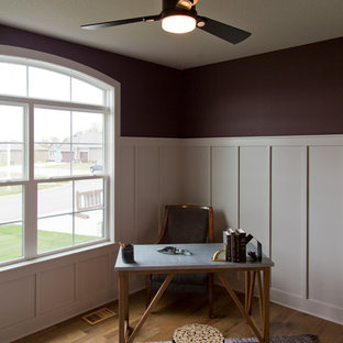Design ideas for a medium sized rustic home office in Kansas City with purple walls, medium hardwood flooring, a freestanding desk and brown floors.