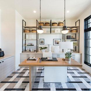 Пример оригинального дизайна: большой кабинет в стиле современная классика с белыми стенами, ковровым покрытием, отдельно стоящим рабочим столом и разноцветным полом без камина