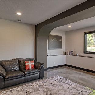 Mittelgroßes Mid-Century Arbeitszimmer mit Betonboden, grauem Boden und freigelegten Dachbalken in Minneapolis
