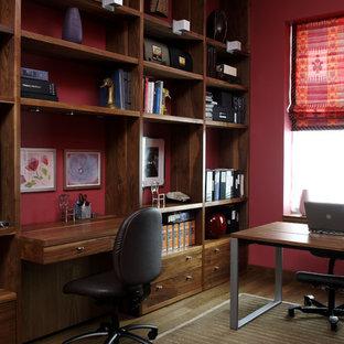 ニューヨークのコンテンポラリースタイルのおしゃれなホームオフィス・書斎 (造り付け机、赤い壁) の写真