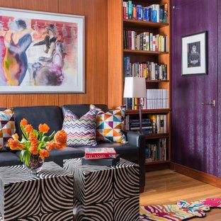 Immagine di uno studio minimal di medie dimensioni con libreria, pareti viola, pavimento in legno massello medio e nessun camino