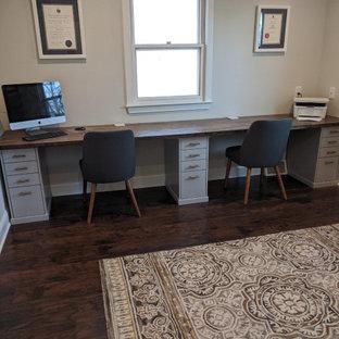 フィラデルフィアの中くらいのモダンスタイルのおしゃれなホームオフィス・書斎 (グレーの壁、ラミネートの床、造り付け机、茶色い床) の写真