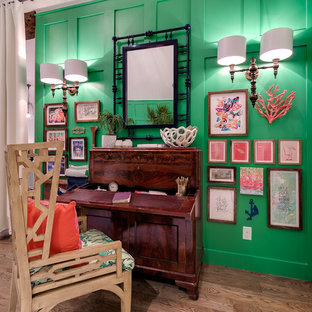 Cette image montre un bureau ethnique de type studio avec un mur vert, un sol en bois clair et un bureau indépendant.