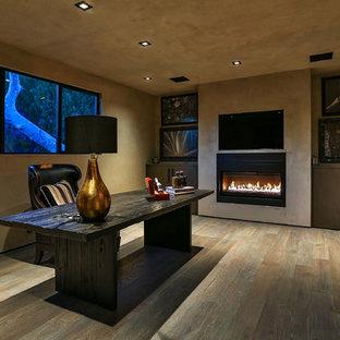 ロサンゼルスの中サイズのコンテンポラリースタイルのおしゃれな書斎 (ベージュの壁、淡色無垢フローリング、横長型暖炉、自立型机、コンクリートの暖炉まわり、茶色い床) の写真