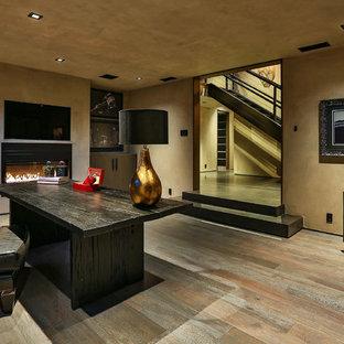 Diseño de despacho contemporáneo, de tamaño medio, con paredes beige, suelo de madera clara, chimenea lineal, marco de chimenea de hormigón, escritorio independiente y suelo marrón