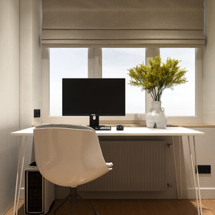 Exempel på ett litet modernt hemmabibliotek, med vita väggar, ljust trägolv, ett fristående skrivbord och gult golv