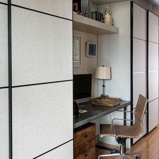 Inredning av ett modernt litet hemmabibliotek, med grå väggar, ljust trägolv, ett fristående skrivbord och gult golv
