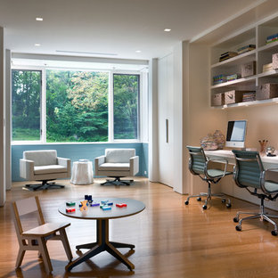 Example of a transitional built-in desk medium tone wood floor study room design in New York