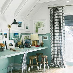 Cette image montre un petit bureau bohème de type studio avec un mur multicolore, un sol en bois brun et un bureau intégré.