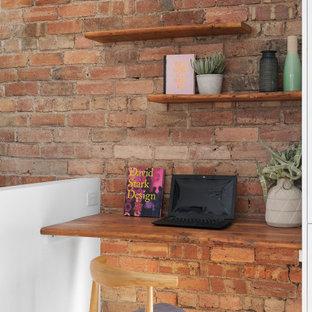 Bild på ett litet industriellt arbetsrum, med röda väggar, ljust trägolv och ett inbyggt skrivbord