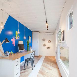 オースティンの中くらいのコンテンポラリースタイルのおしゃれなホームオフィス・書斎 (青い壁、淡色無垢フローリング、暖炉なし、自立型机) の写真