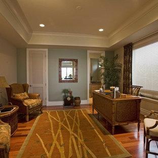 ハワイの大きいトロピカルスタイルのおしゃれなホームオフィス・仕事部屋 (緑の壁、無垢フローリング、暖炉なし、自立型机、茶色い床) の写真