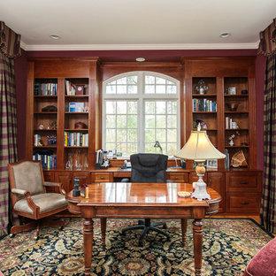 ボストンの中サイズのトラディショナルスタイルのおしゃれなホームオフィス・仕事部屋 (ライブラリー、赤い壁、無垢フローリング、自立型机、マルチカラーの床) の写真