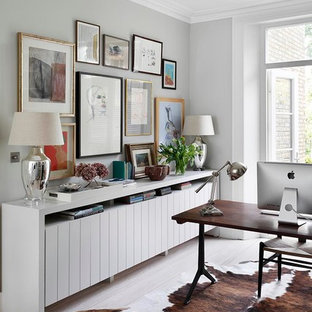 Study room - transitional freestanding desk light wood floor study room idea in London with gray walls
