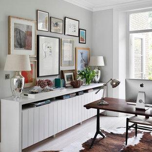 Ejemplo de despacho clásico renovado con paredes grises, suelo de madera clara y escritorio independiente