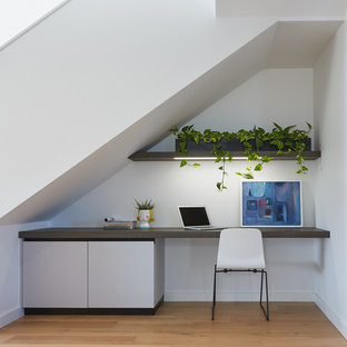 Photo of a mid-sized contemporary study room in Perth with white walls, light hardwood floors, a built-in desk and beige floor.