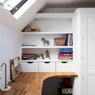Foto på ett mellanstort funkis hemmabibliotek, med vita väggar, ett inbyggt skrivbord, heltäckningsmatta, en standard öppen spis, en spiselkrans i trä och beiget golv