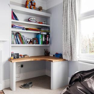 На фото: рабочее место среднего размера в современном стиле с белыми стенами, ковровым покрытием, стандартным камином, фасадом камина из плитки, встроенным рабочим столом и бежевым полом с