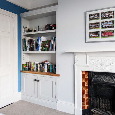Study room - mid-sized contemporary built-in desk carpeted and beige floor study room idea in Kent with white walls, a standard fireplace and a tile fireplace