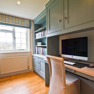他の地域の中くらいのコンテンポラリースタイルのおしゃれな書斎 (グレーの壁、ラミネートの床、暖炉なし、造り付け机) の写真