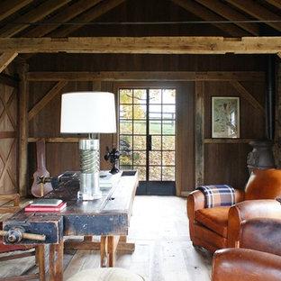 Lantlig inredning av ett mellanstort arbetsrum, med en öppen vedspis, ett fristående skrivbord, bruna väggar och ljust trägolv