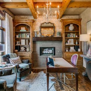 Inspiration för klassiska hemmabibliotek, med grå väggar, mörkt trägolv, en standard öppen spis, ett fristående skrivbord och brunt golv