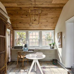 Diseño de despacho campestre, de tamaño medio, con paredes beige, suelo de pizarra, escritorio empotrado y suelo multicolor