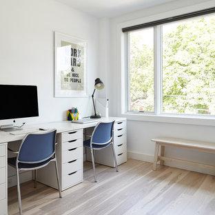 Idee per un piccolo atelier moderno con pareti bianche, parquet chiaro, scrivania autoportante e pavimento multicolore