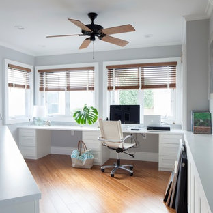 Example of an island style built-in desk medium tone wood floor home office design in Hawaii with gray walls