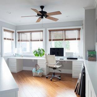 Immagine di uno studio tropicale con pareti grigie, pavimento in legno massello medio e scrivania incassata