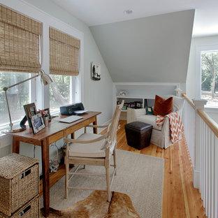 Cette photo montre un bureau exotique avec un mur gris, un sol en bois brun et un bureau indépendant.