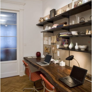 Mid-sized eclectic built-in desk medium tone wood floor and brown floor home office photo in New York with white walls and no fireplace