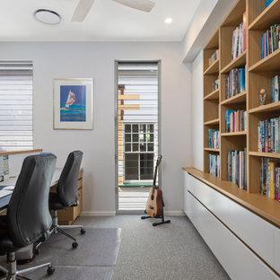 Imagen de despacho madera, costero, pequeño, madera, con paredes blancas, moqueta, escritorio empotrado, suelo gris y madera