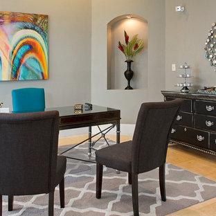 Diseño de despacho actual, grande, sin chimenea, con suelo de travertino, escritorio independiente y paredes grises