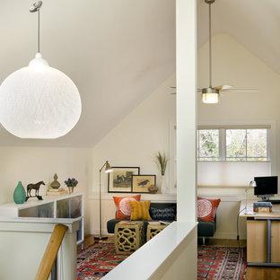 Trendy freestanding desk medium tone wood floor home office photo in Boston with white walls