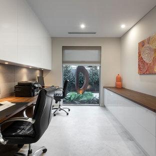 Modelo de despacho actual, grande, sin chimenea, con paredes grises, suelo de piedra caliza, escritorio empotrado y suelo gris