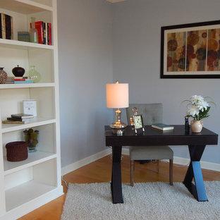 Foto di un ufficio minimal con pareti viola, pavimento in legno massello medio e scrivania autoportante