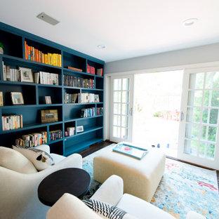 Inredning av ett modernt mellanstort arbetsrum, med ett bibliotek, beige väggar, mörkt trägolv, en standard öppen spis och en spiselkrans i betong