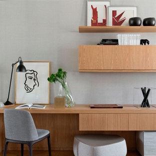 Inredning av ett modernt mellanstort arbetsrum, med grå väggar, mellanmörkt trägolv och ett inbyggt skrivbord