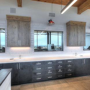 シアトルのモダンスタイルのおしゃれなホームオフィス・書斎 (白い壁、ラミネートの床、造り付け机、グレーの床) の写真