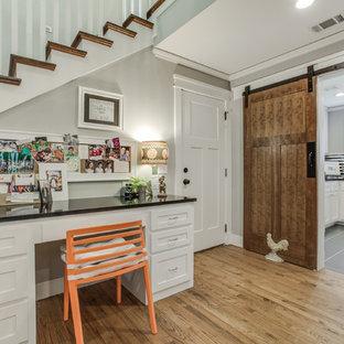 Cette image montre un petit bureau atelier craftsman avec un sol en bois clair, aucune cheminée et un bureau intégré.