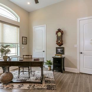 Foto di un ufficio chic di medie dimensioni con pareti beige, pavimento in gres porcellanato, camino classico, cornice del camino in pietra e scrivania autoportante