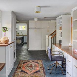 Modelo de despacho tradicional renovado, de tamaño medio, con paredes blancas, escritorio empotrado, suelo gris y suelo de pizarra